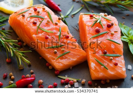 Fresh uncooked salmon fillets with rosemary and pepper on black stone background
