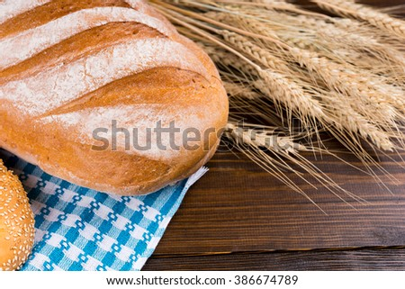 Fresh uncut large crusty French baguette with ears of golden ripe wheat on a wooden table, close up view - stock photo
