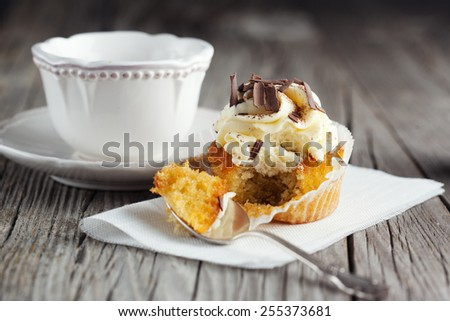 Fresh vanilla cupcake decorated with creamy chocolate cream on old wooden background, selective focus - stock photo