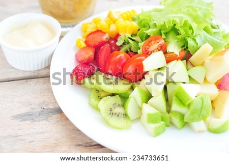 fresh vegetable and fruits salad on dish. - stock photo