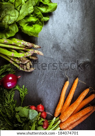 Fresh vegetable frame or border on textured slate with copyspace for your text with farm fresh bunches of asparagus spears, carrots, radish spinach and beetroot - stock photo