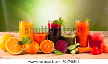 Fresh vegetable juices on wood plant and green background - stock photo