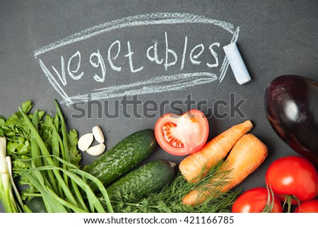 Fresh vegetable on graphite board with an inscription. Top view. onion, garlic , parsley , cucumber , eggplant , tomato and dill - stock photo
