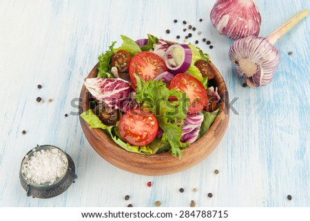 fresh vegetable salad in a bowl and garlic - stock photo