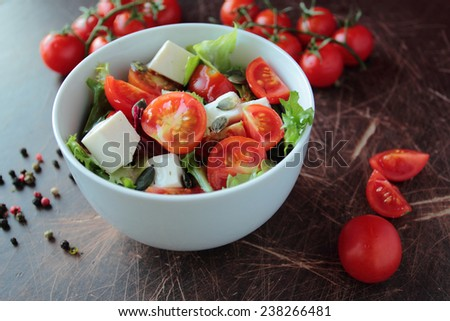 Fresh vegetable salad in a bowl on wooden kitchen table - stock photo