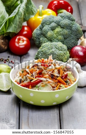 Fresh vegetable salad in green dotted bowl. Raw vegetables and fruits in the background. - stock photo