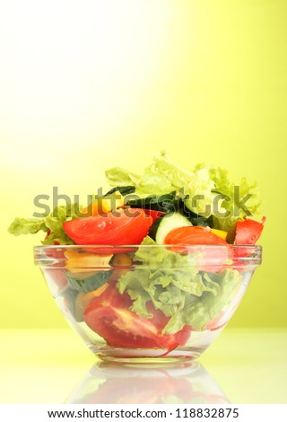 fresh vegetable salad in transparent bowl on green background