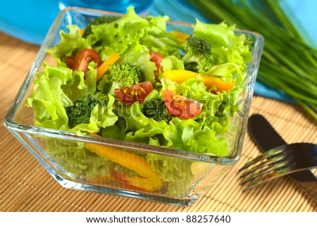 Fresh vegetable salad made of tomato, broccoli, corn, yellow bell pepper and lettuce (Selective Focus, Focus on the tomato and the two broccoli florets in the front)