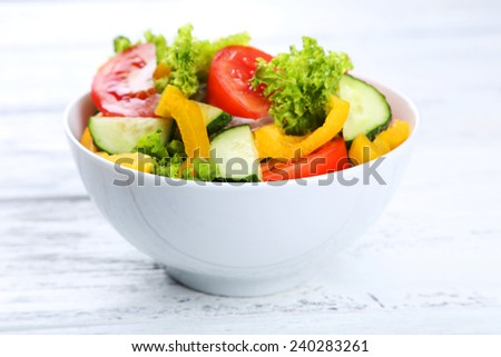 Fresh vegetable salad on white wooden background - stock photo