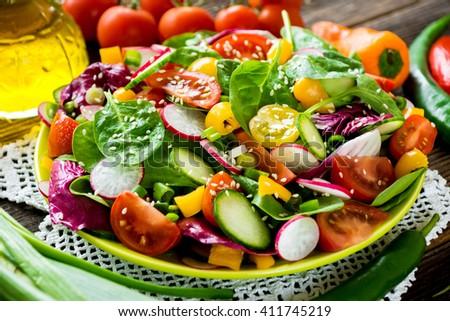 Fresh vegetable salad on wooden background - stock photo