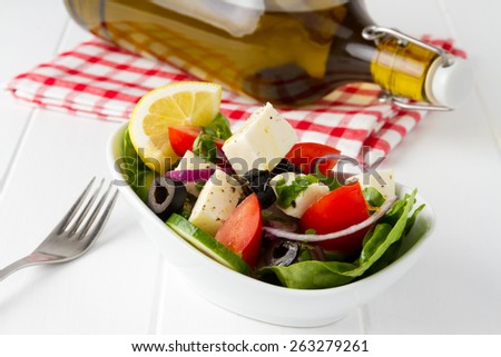 Fresh vegetable salad prepared from lettuce, tomatoes, black olives, cucumber, lemon, olive oil and red onion - stock photo