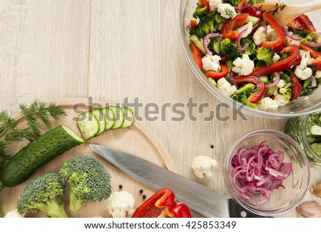 Fresh vegetable salad with broccoli, cauliflower, marinated cucumbers, marinated red onions, sweet red pepper and dill. Fully raw food. - stock photo
