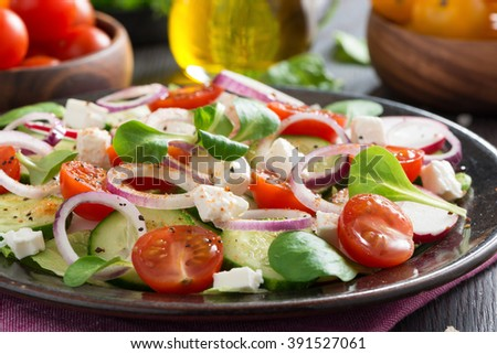 fresh vegetable salad with feta cheese on a plate, selective focus, close-up