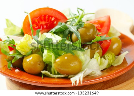 Fresh vegetable salad with green olives on a ceramic plate