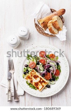 Fresh vegetable salad with grilled cheese on white wooden background - stock photo