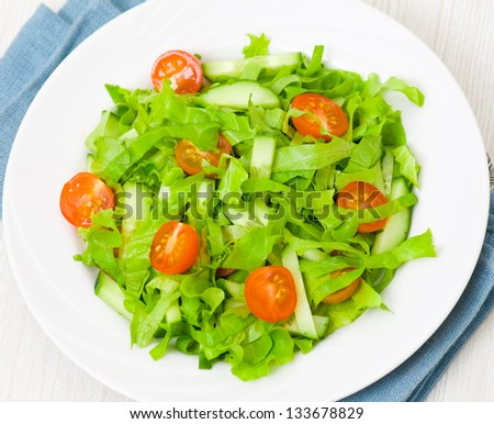 fresh vegetable salad with lettuce, tomato and cucumber - stock photo