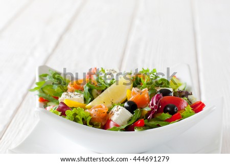 Fresh vegetable salad with salmon in white bowl copyspace. Front view on white ceramic bowl with tasty salad with salmon, brie, olives and slice of lemon on white wooden background. Free space - stock photo