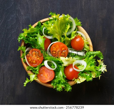 Fresh vegetable salad with tomato, endive and onion. Top view. Selective focus. Space for text. - stock photo