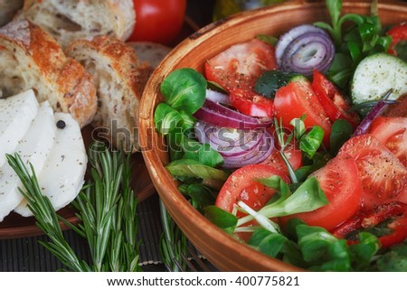 Fresh vegetable salad with tomatoes, cucumbers and onions. Served with cheese, vegetables, olive oil and bread