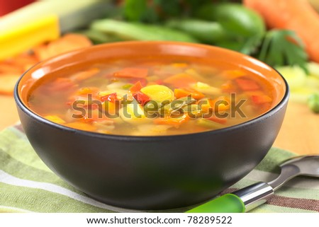 Fresh vegetable soup made of bean, pea, carrot, potato, red bell pepper, tomato and leek in black bowl with ingredients in the back (Selective Focus, Focus on the vegetables in the middle of the soup) - stock photo