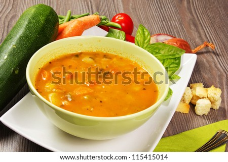 Fresh vegetable soup made of green bean, pea, carrot, potato, red bell pepper, tomato and leek in bowl with parsley in the back (Selective Focus, Focus on the vegetables one third into the soup)