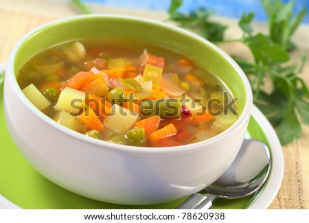 Fresh vegetable soup made of green bean, pea, carrot, potato, red bell pepper, tomato and leek in bowl with parsley in the back (Selective Focus, Focus on the vegetables one third into the soup) - stock photo