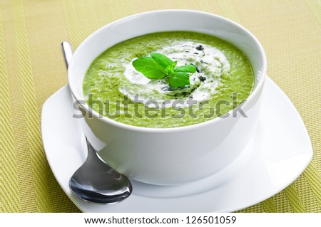 Fresh vegetable soup topped with cream and mint - stock photo