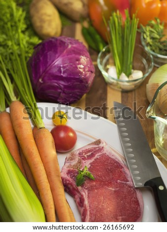 fresh vegetables and a raw steak flayed out on a cutting board with a knife, morning or early evening light coming through the window. - stock photo