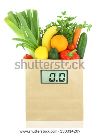 Fresh vegetables and fruits in a paper grocery bag with digital diet scale - stock photo