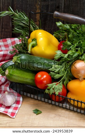 Fresh vegetables and herbs in metal basket: bell peppers, zucchini, onions, tomatoes, garlic, parsley, thyme and rosemary - stock photo