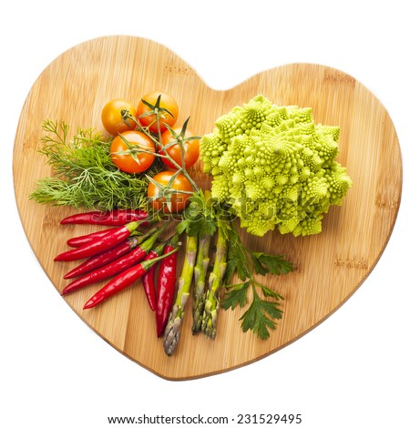 Fresh vegetables and herbs lie on a wooden board in a heart shape Isolated on white background - stock photo