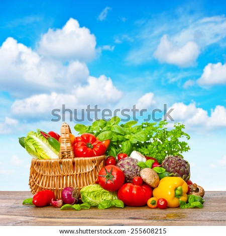 Fresh vegetables and herbs on wooden background over beautiful blue sky. Shopping basket with organic food ingredients - stock photo