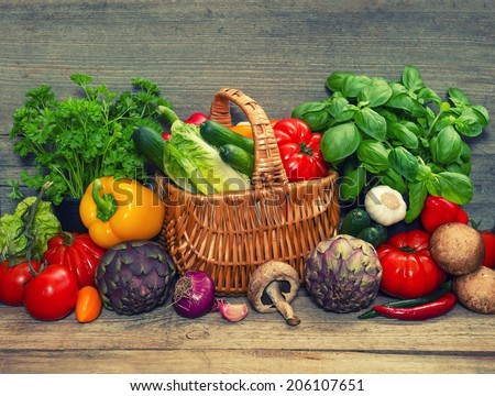 fresh vegetables and herbs on wooden background. raw food ingredients. retro style toned picture - stock photo