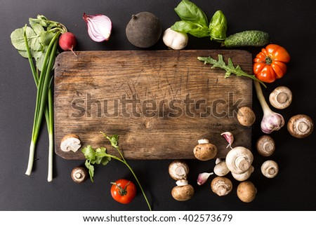 fresh vegetables and ingredients for cooking around vintage cutting board on black background - stock photo