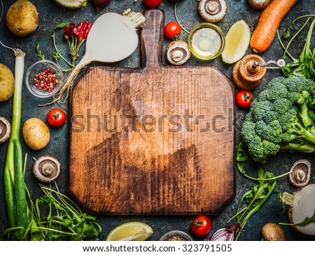Fresh vegetables and  ingredients for cooking around vintage cutting board on rustic background, top view, place for text.  Vegan food , vegetarian and healthily cooking concept. - stock photo