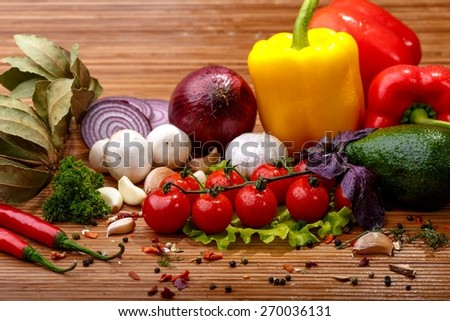 Fresh vegetables and spices: tomatoes, peppers, mushrooms, herbs, avocado on wooden background - stock photo