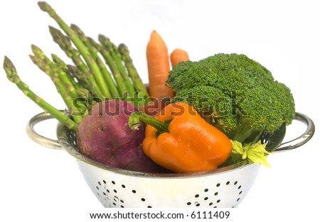 Fresh vegetables - asparagus, carrots, broccoli, sweet potato  and capsicum in steel colander with water drops. On white background, isolated. Shallow DoF. - stock photo