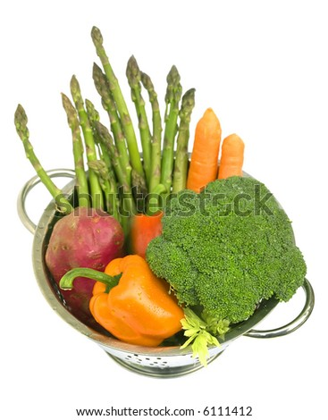 Fresh vegetables - asparagus, carrots, broccoli, sweet potato and capsicum in steel colander with water drops. On white background, isolated. Shallow DoF. Top view. Vertical direction. - stock photo