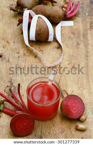 fresh vegetables beetroot juice and a tape measure