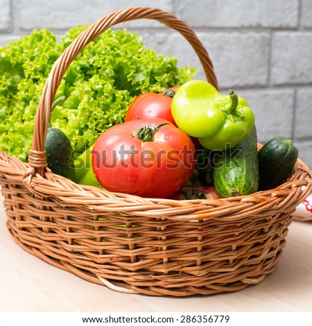 Fresh vegetables covred with water drops in basket. Organic Tomatoes, cucumber, pepper and vibrant green lettuce from the market. Fresh raw food.