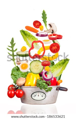 fresh vegetables falling into a rustic pot with weight scale, zero calories, diet