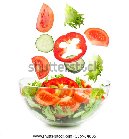 Fresh vegetables falling into the glass bowl isolated over white background - stock photo