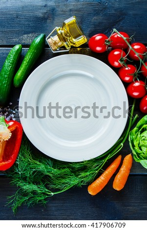 Fresh vegetables for tasty vegan and diet cooking or salad making around empty plate on rustic wooden background, top view. Vegetarian food concept. - stock photo