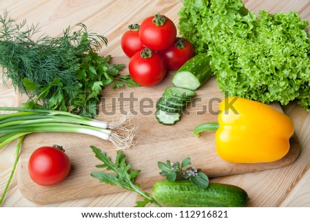 Fresh vegetables, herbs and spices on a cutting board.