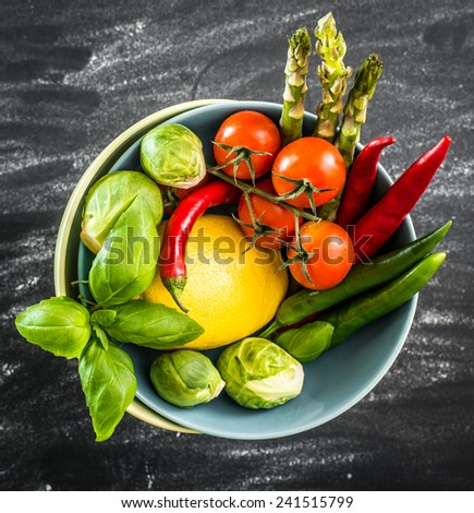 Fresh vegetables in a blue bowl on a black table - stock photo