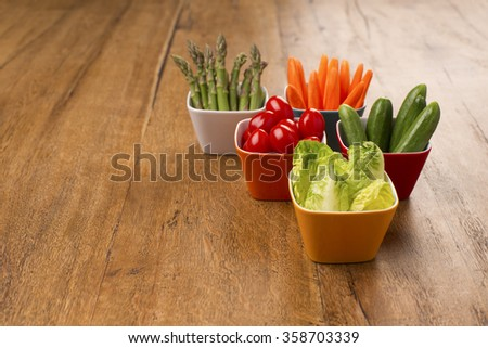 Fresh vegetables in colourful bowls on a wooden table with copy space. Healthy party snacks. Asparagus, cucumbers, carrots, lettuce leaves and cherry tomatoes.  - stock photo