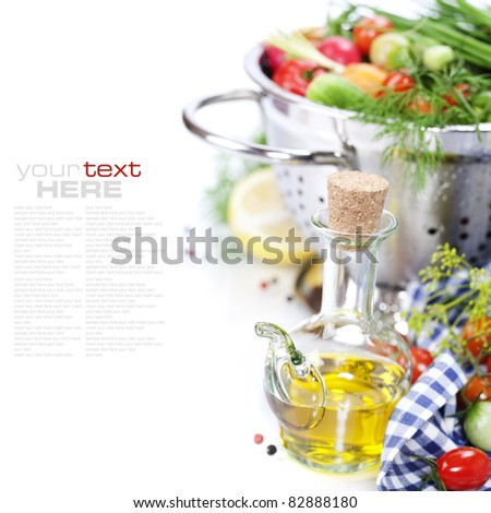 Fresh vegetables in metal colander and olive oil over white (with sample text) - stock photo