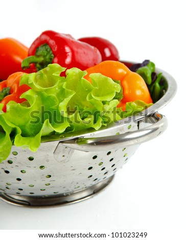 Fresh vegetables in metal colander over white - stock photo