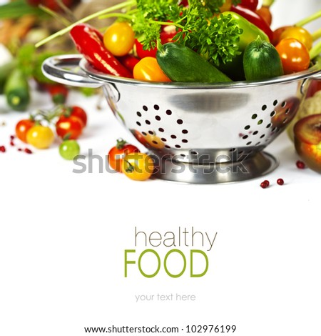 Fresh vegetables in metal colander over white (with easy removable text) - stock photo