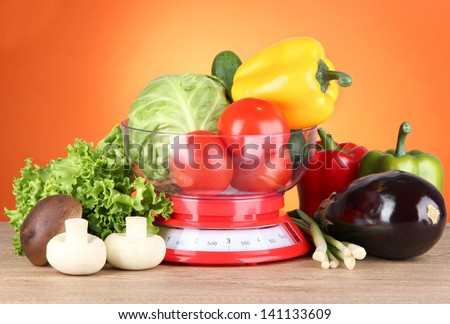 Fresh vegetables in scales on table on orange background